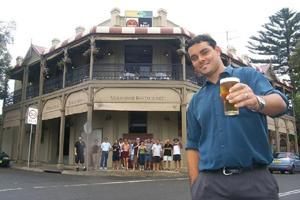 Balgownie publican Joel Jarvis and regular drinkers (under the balcony) raise their glasses to a century of trading in 2004.